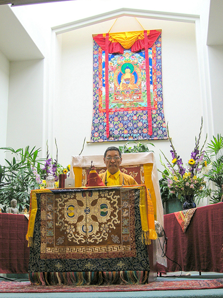 Gangteng Rinpoche teaching before a large appliqué thangka by Leslie Rinchen-Wongmo at Unity Church in Santa Barbara, CA in 2014