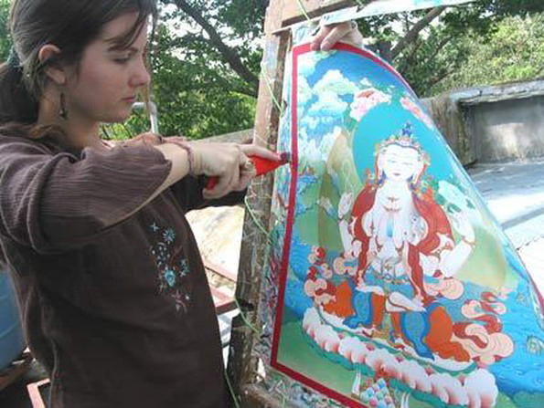 Tiffani Gyatso, a member of the Dakini As Art collective, cuts her completed thangka painting from its stretcher frame. Next it will be framed in brocade. See more of Tiffani's artwork at tiffanigyatso.com.