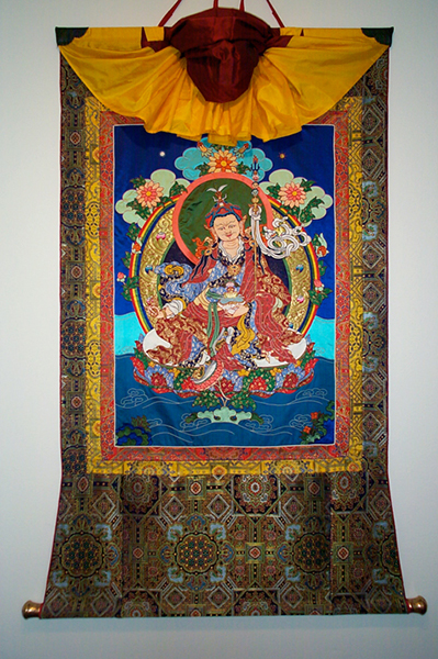 "Guru Rinpoche appliqué thangka by Leslie Rinchen-Wongmo. Notice the ""rainbow"" strips of brocade surrounding the image, the slat at the top of the frame, dowel at the bottom, and veil decoratively arranged at the top."