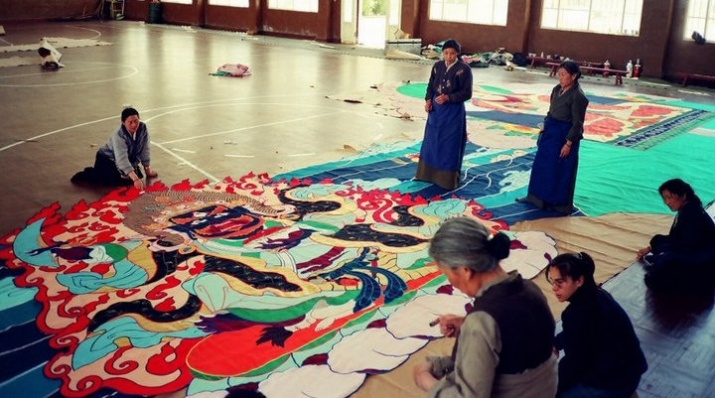 Tibetan women working on the giant thangka. As the image grew in size, a gymnasium was used to assemble the completed parts. Image courtesy of Leslie Nguyen Temple