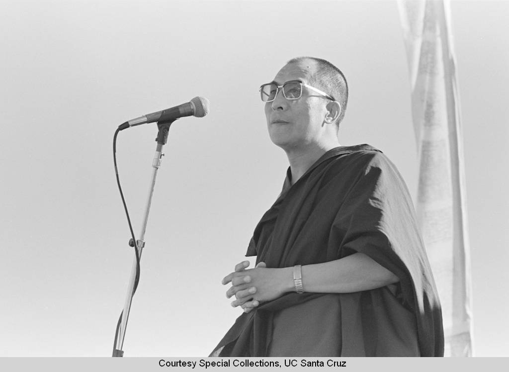 Dalai_Lama_visits_UC_Santa_Cruz_October_1979_the_Dalai_Lama_at_the_microphone_at_the_stage_on_the_East_Field